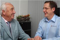 Der Hausarzt Dr. Möllemann mit Patient in einer Reiseberatung