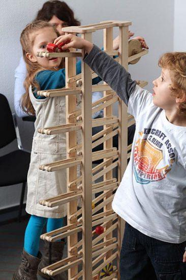 Kinder spielen im Wartezimmer mit der Kugelbahn